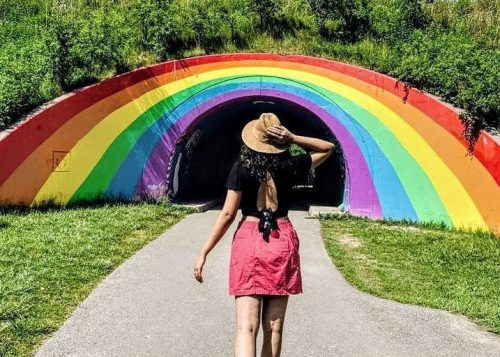 A woman in a straw hat walking in a rainbow painted pedestrian tunnel.