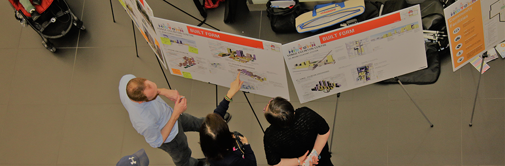 Members of the public pointing to a display board during a public meeting event.
