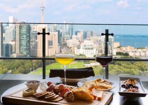 Two glasses of beverages, charcuterie board and other appetizers on a balcony table with Toronto's skyline in the background.