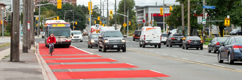 Image of Eglinton showing 4 lanes of traffic. The curb side lanes in each direction are painted red to indicate that only buses are allowed to use the lane.
