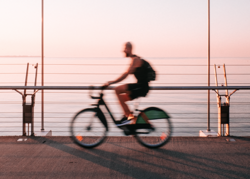 Motion blur photograph of a person riding a bike along the Lake Ontario shore at sunset.
