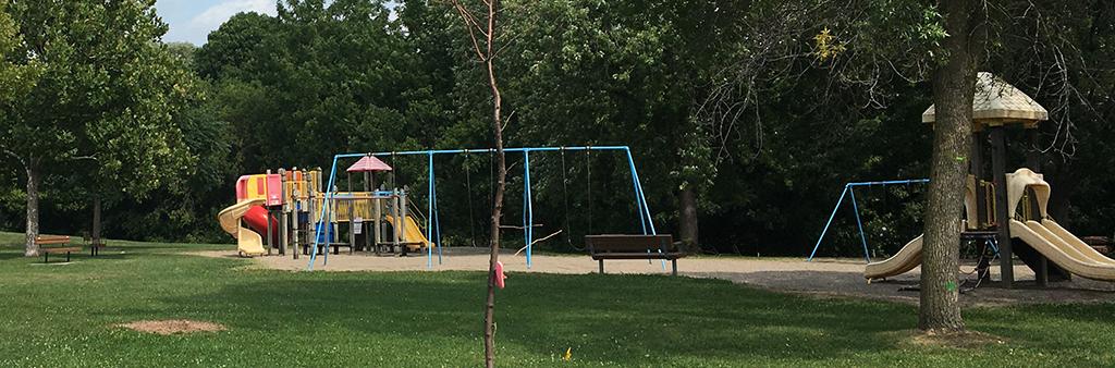 Exbury Park Playground, including the climbing equipment and swings.