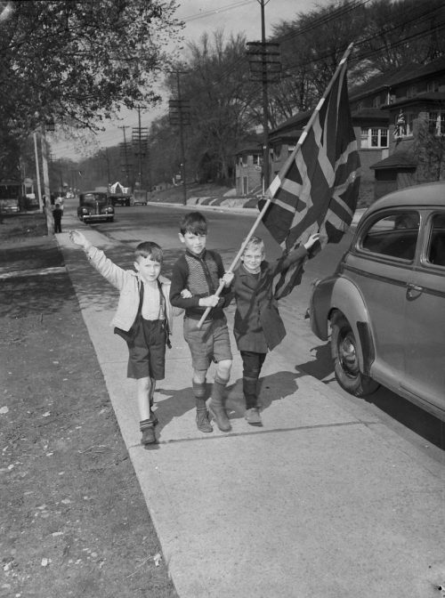 Photograph of 3 children with Union Jack, celebrating VE Day.