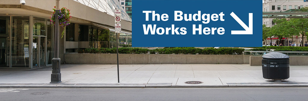 """Street garbage bin with arrow that says """"The Budget Works Here"""""""
