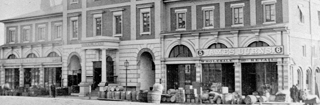Black and white photograph showing the main entrance and the arched windows of street-level shops at the Front Street City Hall. Barrels and crates piled up on the sidewalk in the foreground