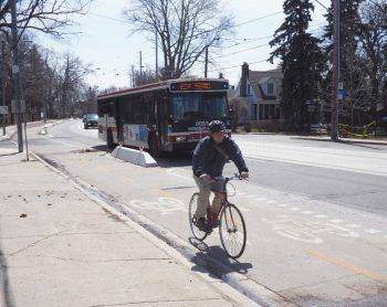 Photo of a cyclist riding in a separated bike lane with pre-cast concrete barriers with reflectors