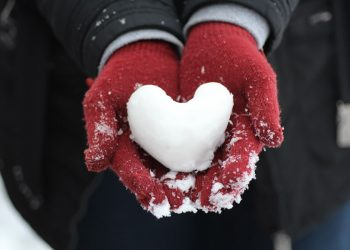 A person in red gloves holding heart shape made from snow