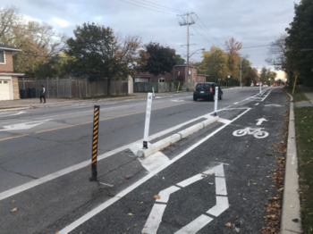 Photo showing separated bike lane with pre-cast concrete curbs and flexible posts
