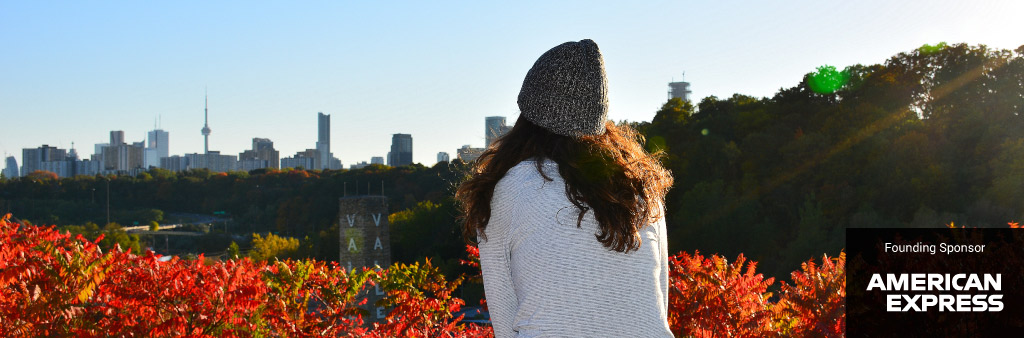 Woman looking at Toronto city skyline with fall colored foliage in foreground