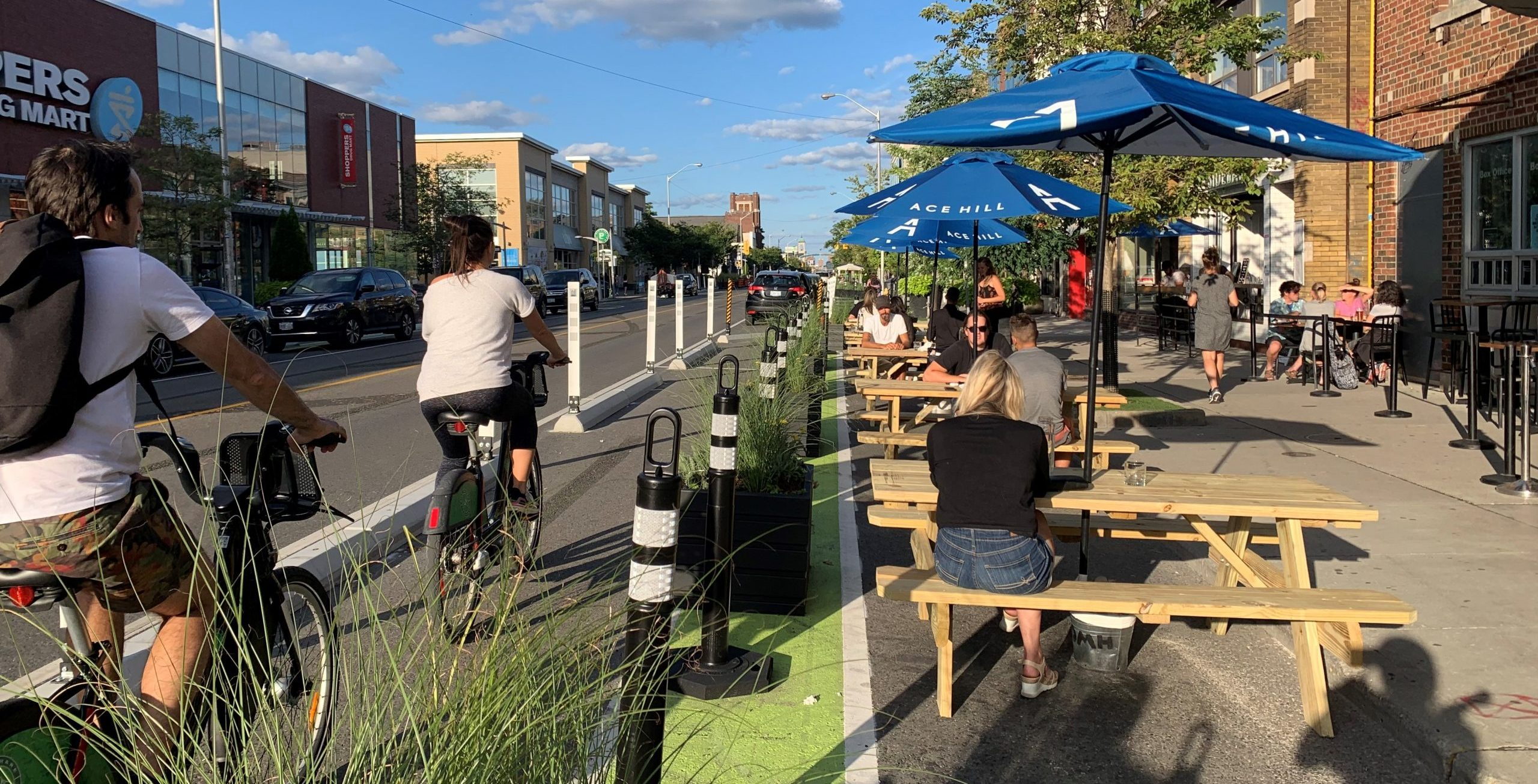 Image of Danforth Avenue after the bike lane installation with painted bike lanes separated by planters, bollards and concrete barriers. To the right of the bike lanes are curb lane patios with seating.