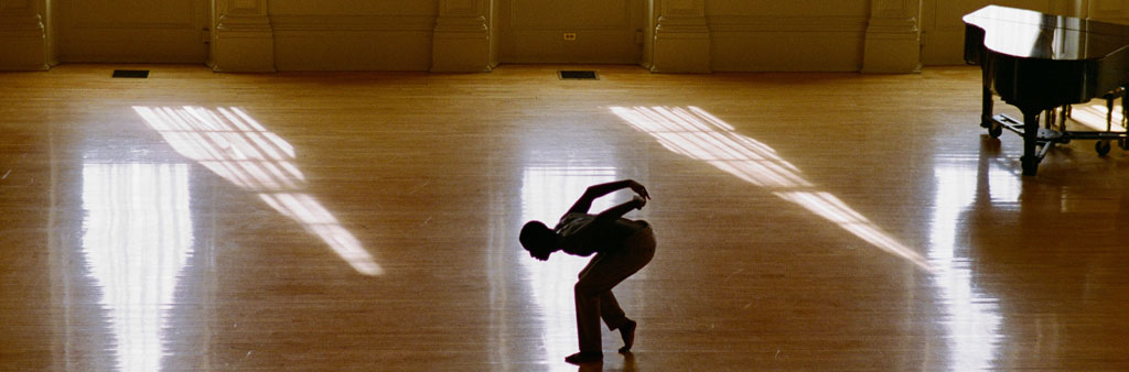 Person dancing in a sunlit gymnasium.