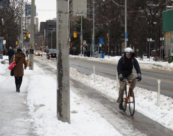Photo showing a cyclist using a cycle track with snow stored at the curb and in the buffer