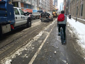 Photo showing a buffered bike lane with a cyclists and snow piled at the curb.