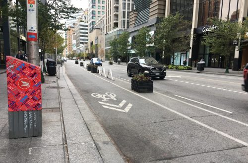 Image of Bloor Street after the bike lane installation with painted bike lanes separated by planters