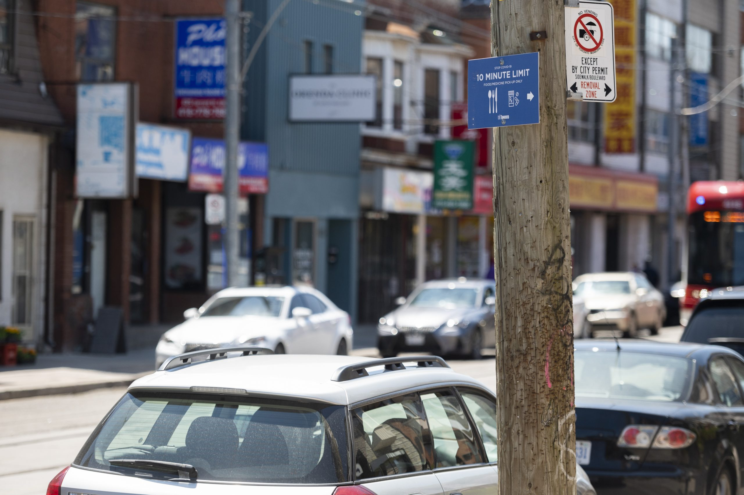 Image of temporary parking pick up zone with blue signage on a pole reading 10 minute limit