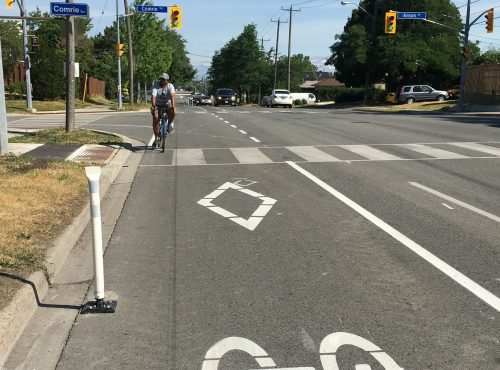 Image of Brimley Road after the bike lane installation with painted bike lanes separated by bollards