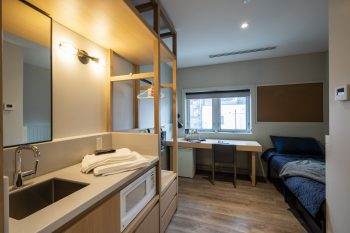 kitchenette in bedroom, includes a sink and microwave.