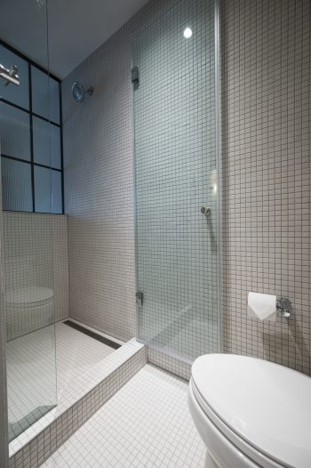 glass shower door in white tile bathroom.