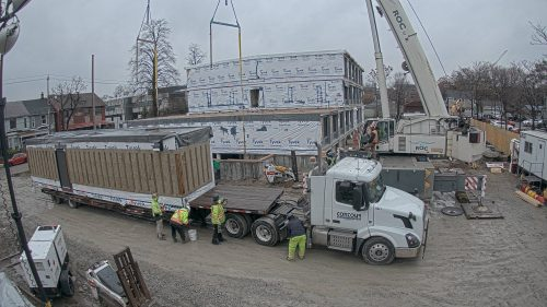 a truck is on site carrying a module at 150 Harrison
