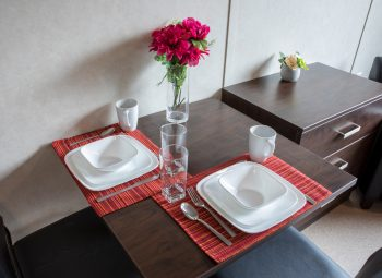 Dining table with cutlery and dishware on dining table.