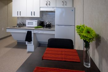 321 Dovercourt Rd. dining table with flowers and view of kitchen fridge and sink.