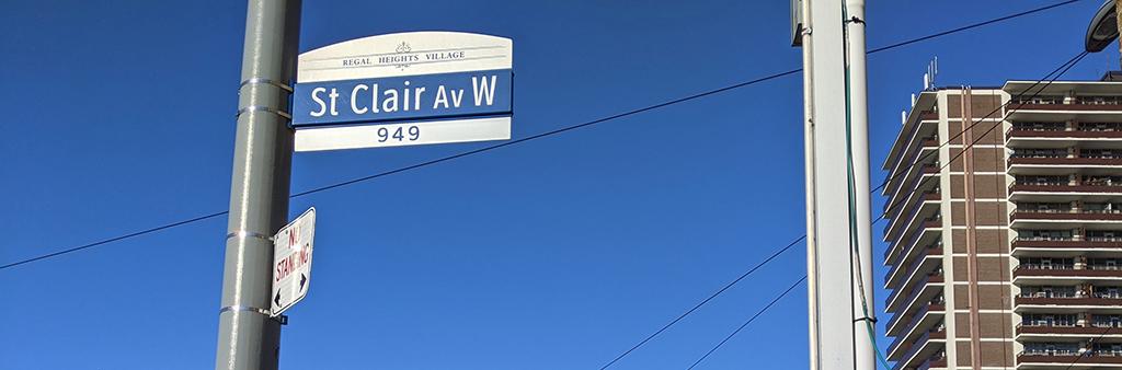 St. Clair Av W street sign against a clear blue sky.