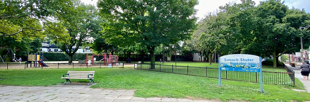Photograph of Sumach-Shuter Parkette. In the background are large trees and colouful playground equipment. In the foreground is a bench and a path on a grassy area. On the right is a City of Toronto park sign that reads Sumach-Shuter Parkette.