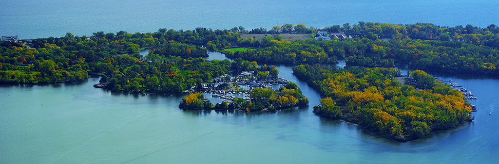 Aerial photograph of Toronto Island in the summer, showing the Toronto Island Marina, green trees and Lake Ontario.