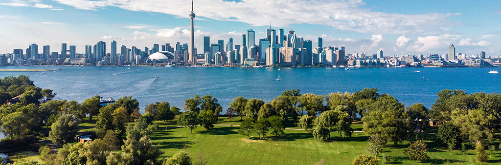 Aerial photograph showing grass and trees in Toronto Island Park, Lake Ontario and the Toronto skyline.