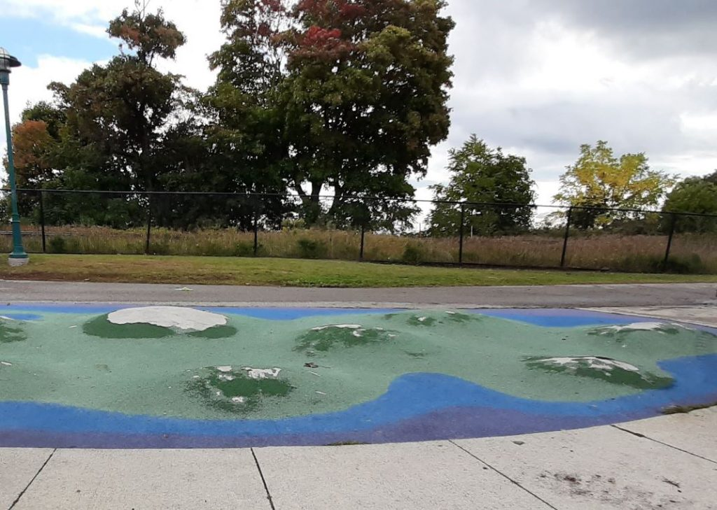 An image of the rubber and concrete mounds located in Port Union Village Common Park. The mounds are green and blue and are in-between a concrete and asphalt pathway.