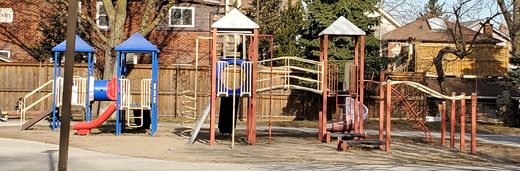 A ground level view of Holley Park Playground which shows the junior and senior play structure on top of sand play surfacing. The playground equipment is blue, red and yellow. A concrete path surrounds the playgrounds including a few mature trees.