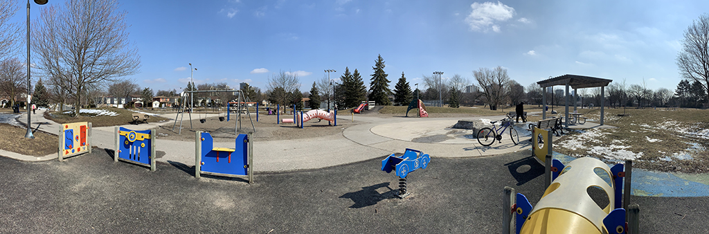 A ground level view of Bellbury Park Playground today, which includes various play elements and structures dispersed across a large area within the park. The playground is surrounded by both mature trees and an open lawn area. The image focuses on the sensory play panels, shade structure with seating and junior swing set.