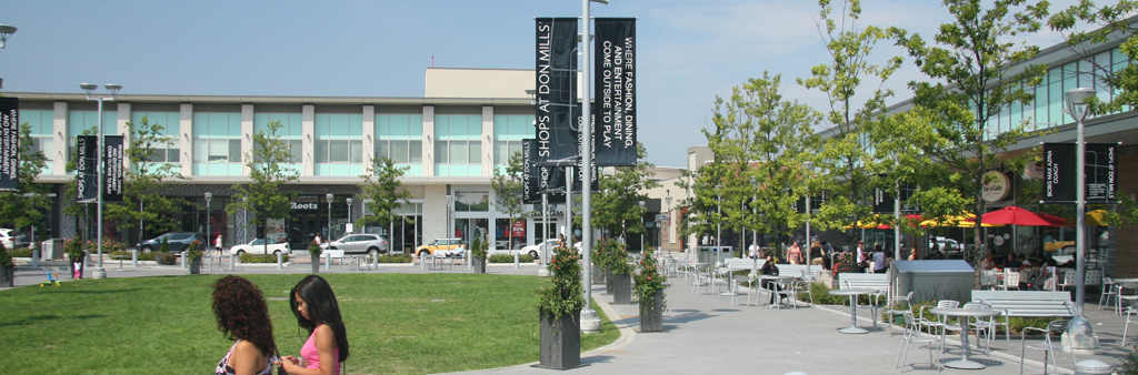 Photo of Shops at Don Mills, showing the central green space, with seating, lighting and signage, and retail uses surrounding it