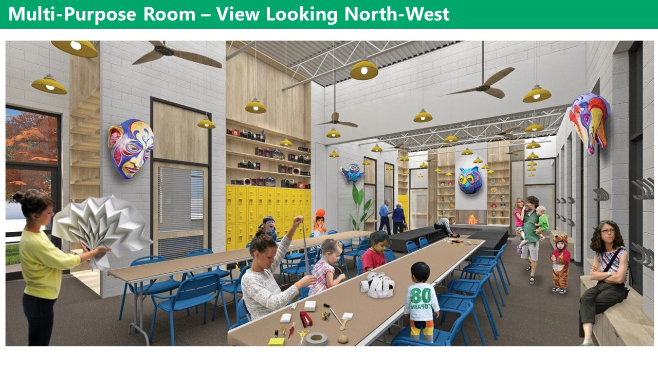 Multi purpose room view looking north-west. The multipurpose room has light grey walls and a dark floor, with high ceilings. There are yellow light fixtures and fans hanging from the ceiling. There are hooks, lockers, and shelves along the walls and long tables with chairs around them in the middle of the room. Along the east wall there are windows with bench seating by the windows.