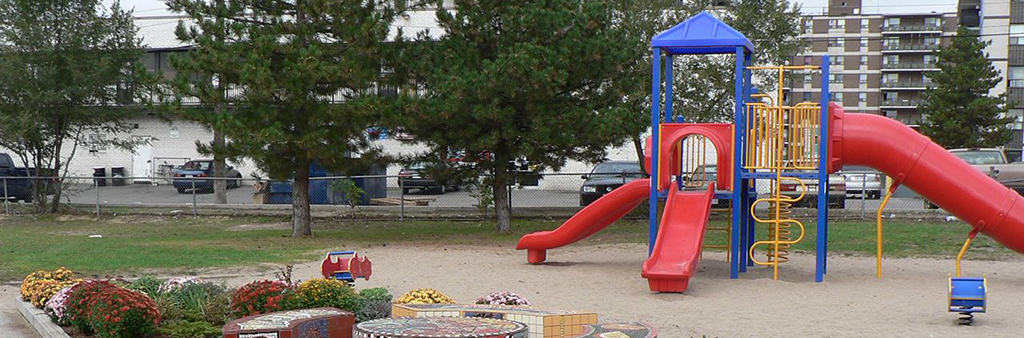 An image of the existing playground at Woolner Park, which includes one play structure with multiple climbing opportunities and three slides. The playground sits on top of sand and has two planting beds beside it.