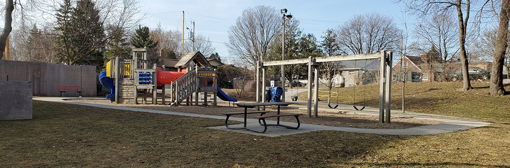 An image of the Upwood Greenbelt Park playground on a sunny day. The play structure sits on top of sand play surfacing and includes a senior play structure and swing set. A small concrete path forms a loop around the playground, with park bench, picnic table and garbage/recycling bins on the perimeter.