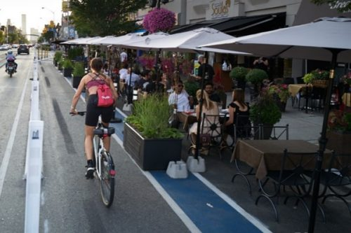 Person riding bicycle in a protected bike lane passing by a cafe patio. The cafe and bike lane are seperated by a painted buffer and planter box.