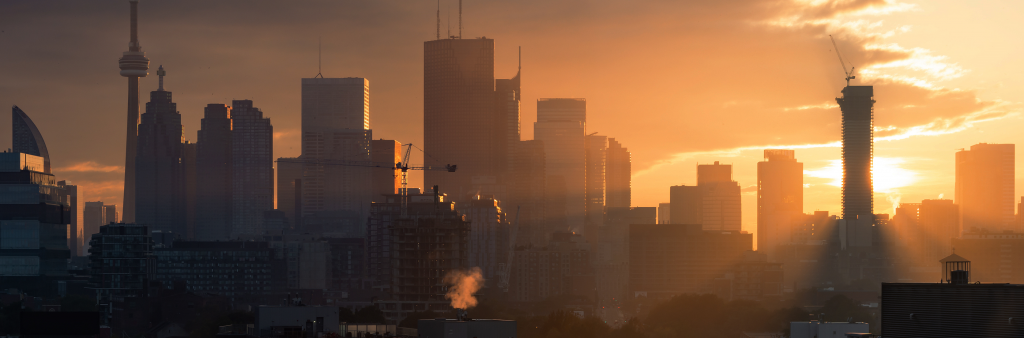 Toronto city skyline at sunset with cranes and construction.