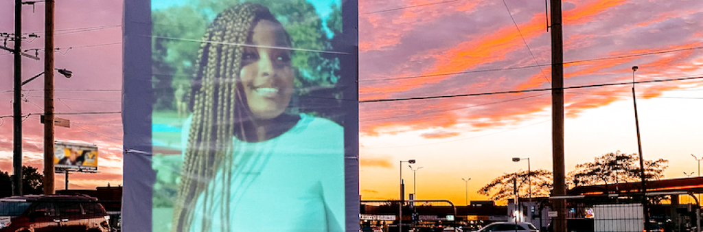 Photographic montage of female wearing white sweater, superimposed over a street scene at dusk.