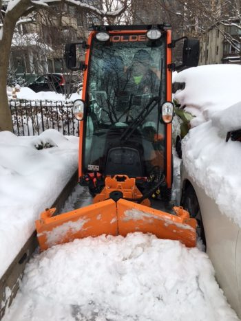 A small plow clearing snow from a tight space between a retaining wall and a parked car.