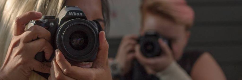 Close-up image of two people with cameras taking photographs, one in-focus in foreground, other out-of-focus in background.
