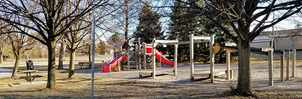 A photograph of Ruddington Park Playground on a sunny day. The playground features two separate structures with various features like slides, monkey bars and seating options. The playground is surrounded by mature trees, sparse grassy areas and a concrete pathway.