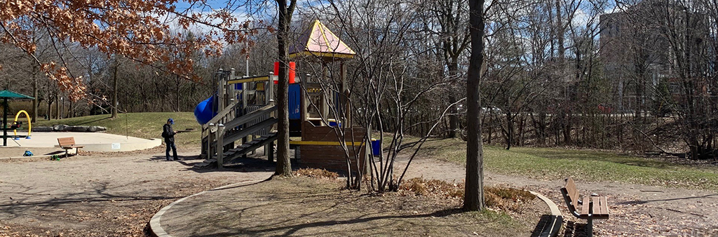 A photograph of the playground taken in March 2021 which shows the medium playground structure surrounded by mature trees and sparse patches of grass.