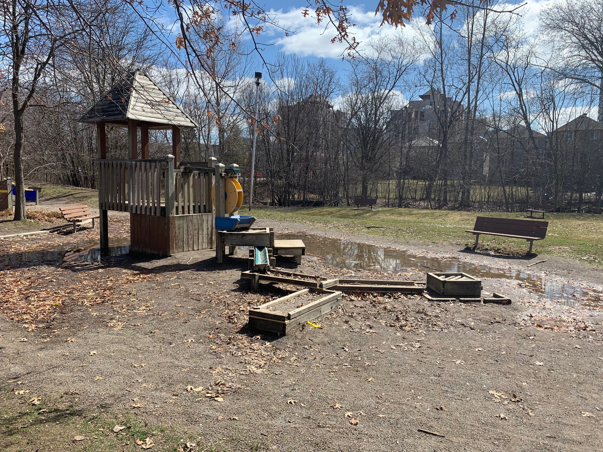 A photograph of the small stand-alone wood structure in the playground with a water mill and wooden channel. Two benches face the play structure. The area is covered in wet sand with some large puddles of water.