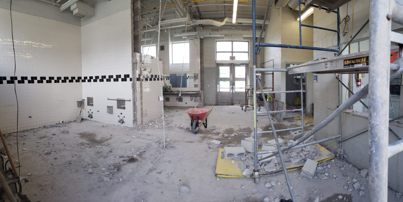 The photo shows the demolition in process inside the clubhouse, where the former washrooms and lobby were located. On the left, the tiled washroom walls are partially removed. On the right, scaffolding is being put up to aid in the demolition.