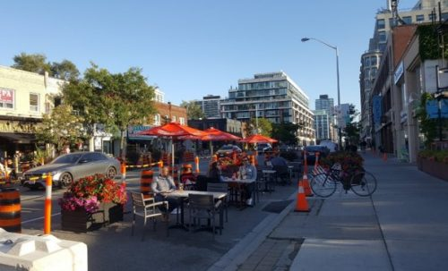 The curb lane shows a row of patio cafes being enjoyed by people on a sunny day.