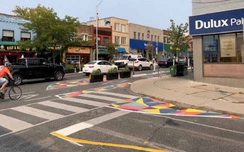 The complete street image shows the use of colourful painted buffers on the street to expand crossing distance for pedestrians.