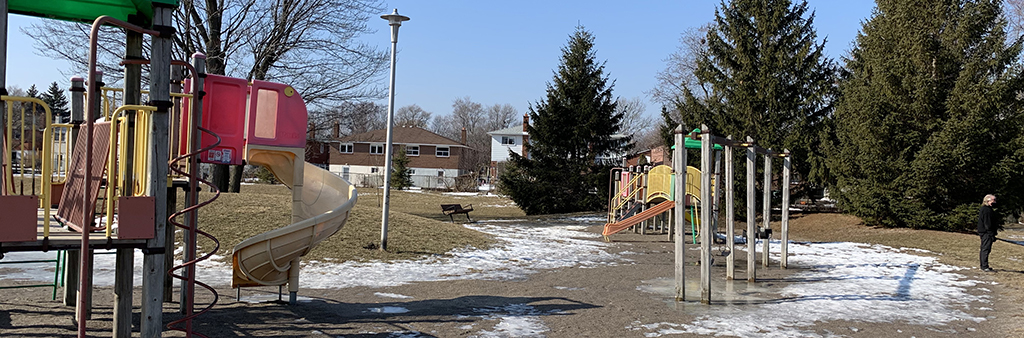 A picture of Pinto Park Playground taken during the winter time. The image shows all three play structures in the playground and the surrounding grass, tall light post and residential homes.