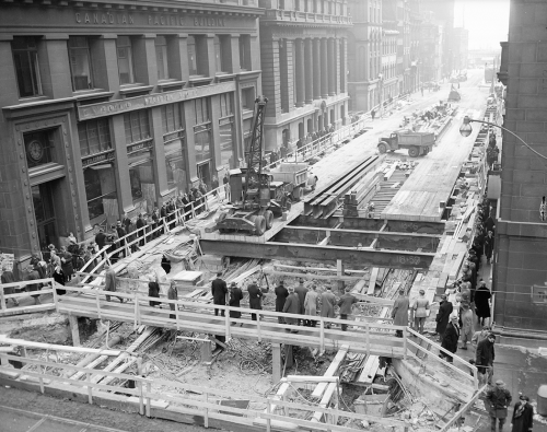 Workers place wooden planks over an excavation to make a roadway. Crowds on both sides of the street are watching them.