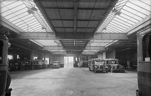 The interior of a large garage with two long skylights in the roof. There are several small buses parked along the sides.